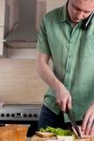 Rijp de mens die een maaltijd voorbereidt stock fotografie