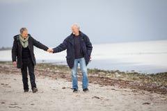 Rijp gelukkig paar die op strand in de herfst lopen Royalty-vrije Stock Foto's
