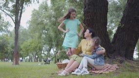 Rijp gelukkige grootmoeder die haar kleindochters onderwijzen terwijl het zitten in het mooie park dichtbij grote groene boom Vro stock videobeelden