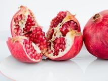 Rijp granaatappelfruit op een plaat van het witeporselein Stock Fotografie