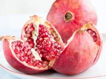Rijp granaatappelfruit op een witte porseleinplaat Stock Afbeelding