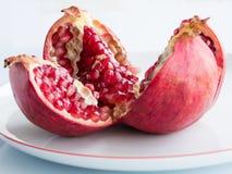Rijp granaatappelfruit op een witte porseleinplaat Stock Afbeeldingen