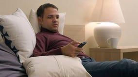 Rijp het knappe mens ontspannen in zijn hotelruimte zoekend iets op TV te letten op stock afbeelding