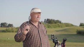 Rijp mensen speelgolf op het golfgebied Hogere mens die wegzettend de club op zijn schouder kijken Oude heer stock videobeelden