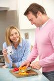 Rijp paar dat maaltijd in binnenlandse keuken voorbereidt Stock Foto