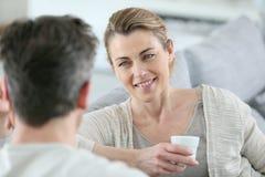 Rijp paar die aan elkaar thuis en het drinken koffie spreken stock foto's