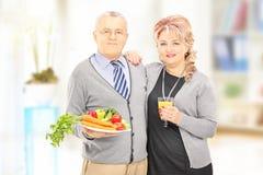 Rijp paar die bevinden zich houdend dicht bij elkaar een gezond voedsel en Royalty-vrije Stock Foto