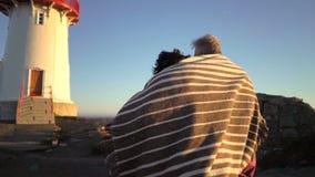 Rijp paar die bij zonsondergang op de kust met een oude vuurtoren lopen stock footage