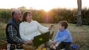 Rijp paar die laptop zitting op plaid met kleinzoon gebruiken bij picknick op achtergrondzonsopgang stock video