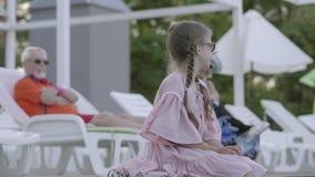 Rijp paar die op sunbeds dichtbij de pool op de achtergrond liggen Weinig grappig meisje die met vlechten op de rand zitten van stock videobeelden