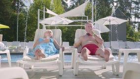 Rijp paar die op sunbeds dichtbij het pool het drinken sap liggen, het spreken en het glimlachen Gelukkige houdende van familie R stock footage