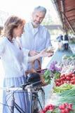 Rijp paar die verse organische groenten in een openluchtmarkt kopen royalty-vrije stock afbeelding