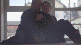 Rijp paar die zitting op de vloer koesteren tegen de achtergrond van een breed venster Familieverhoudingen stock videobeelden