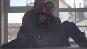 Rijp paar die zitting op de vloer koesteren tegen de achtergrond van een breed venster Familieverhoudingen r stock footage