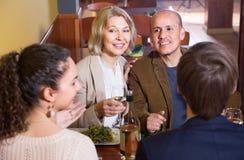 Rijp paar met vrienden die diner en wijn hebben bij restaurant royalty-vrije stock foto's