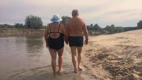 Rijp Paar -- omhels het overzien van rivier Mooi paar van oudsten dichtbij water Oude gelukkige mensen die handen houden stock video