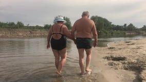 Rijp Paar -- omhels het overzien van rivier Mooi paar van oudsten dichtbij water Oude gelukkige mensen die handen houden stock footage