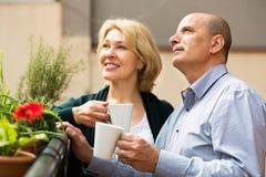 Rijp paar op balkon met koffie stock afbeelding