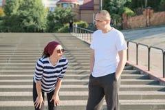 Rijp paar in stad dichtbij de treden, man en vrouw op middelbare leeftijd in sportkleding spreken die na het lopen rusten stock afbeelding