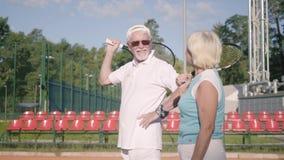 Rijp paar in zonnebril en tennisrackets die zich op een tennisbaan in de zon bevinden Recreatie en vrije tijd in openlucht stock video