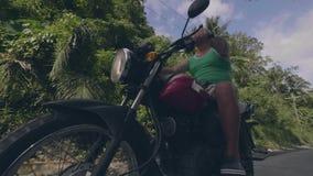 Rijp personenvervoer op motorfiets op weg op groene bos en blauwe hemelachtergrond Lage hoekmening Gepensioneerdemens het drijven stock videobeelden