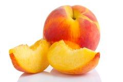 Rijp perzikfruit met plakken op wit Stock Foto's