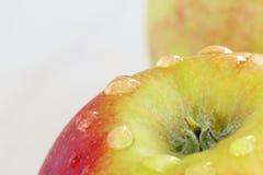 Rijp rood - gele appel op een witte achtergrond met dalingen van water na regen stock afbeeldingen