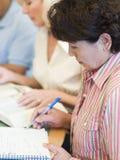 Rijp studenten die in bibliotheek bestuderen Stock Fotografie