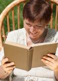 Rijp vrouwenlezing boek en het lachen Stock Foto's