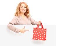 Rijp wijfje die een zak houden en op een leeg paneel gesturing Royalty-vrije Stock Foto