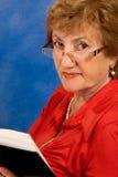 Rijpe aantrekkelijke vrouw die in glazen boek leest Stock Afbeelding