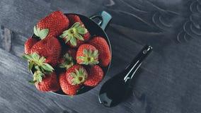 Rijpe aardbeien in kom met lepel op een donkere achtergrond in rustieke stijl De ruimte van het exemplaar Stock Afbeeldingen