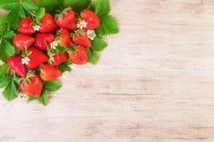 Rijpe aardbeien met blad op bruine heldere achtergrond Tekst ruimte, hoogste mening Stock Fotografie