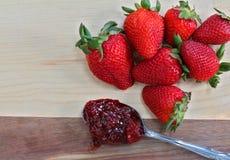 Rijpe aardbeien met een lepel van aardbeijam Macro met mede stock fotografie