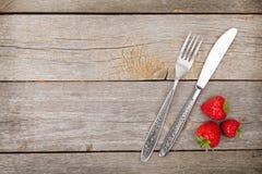 Rijpe aardbeien met tafelzilver over houten lijstachtergrond Royalty-vrije Stock Afbeelding