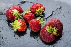 Rijpe aardbeien op zwarte steenachtergrond Stock Foto's