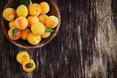 Rijpe abrikozen in een houten kom Stock Afbeelding