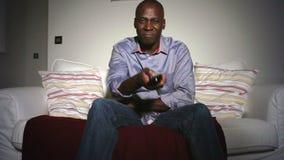 Rijpe Afrikaanse Amerikaanse Mens op Sofa Watching-TV stock video