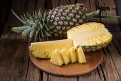 Rijpe ananas en ananasplakken op een houten tropi als achtergrond stock afbeelding