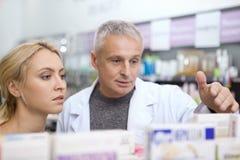 Rijpe apotheker die zijn vrouwelijke klant helpen stock afbeelding