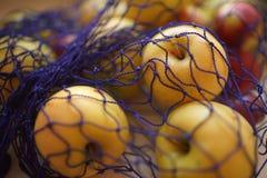 Rijpe appelen in de blauwe netwerkzak, selectieve nadruk royalty-vrije stock foto's