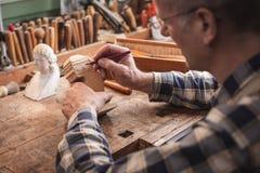 Rijpe artisanaal schetsend de overzichten van een beeldhouwwerk met een potlood stock afbeelding