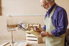 Rijpe artisanaal in speciale kleren maakt nauwkeurige schets stock afbeelding
