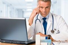 Rijpe arts die bij u staart Stock Afbeelding