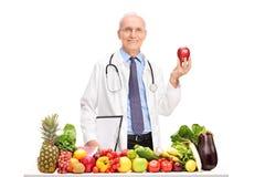 Rijpe arts die een appel houden Stock Foto