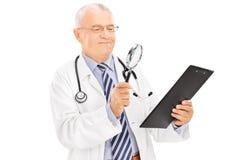 Rijpe arts die een document onderzoeken Stock Afbeeldingen