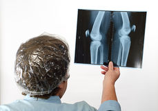 Rijpe arts die het beeld van de Röntgenstraal onderzoekt dichtbij venster royalty-vrije stock fotografie