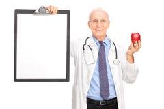 Rijpe arts die rode appel en een klembord houden Royalty-vrije Stock Foto