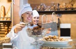 Rijpe bakkerijwerknemer die luim en biscuitgebak aanbieden royalty-vrije stock foto