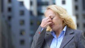 Rijpe bedrijfsvrouw die aan migraine lijden die oogglazen nemen weg, het werkvermoeidheid stock video